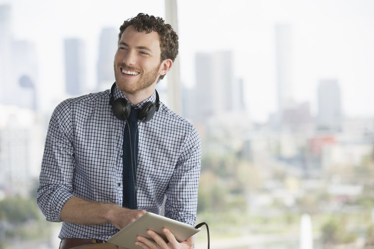 Happy businessman with digital tablet and headphones