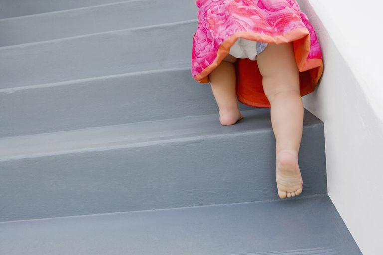 Low section view of a baby girl climbing up staircase