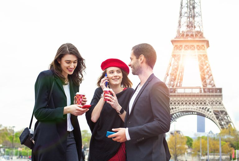 three people talking in front of Eiffel Tower