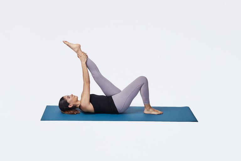 woman stretching hamstring lying on mat