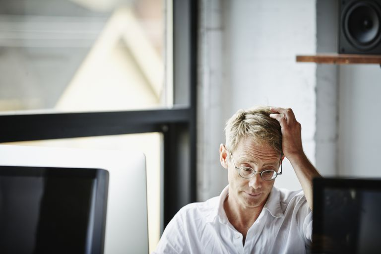 Businessman with hand on head working on computer