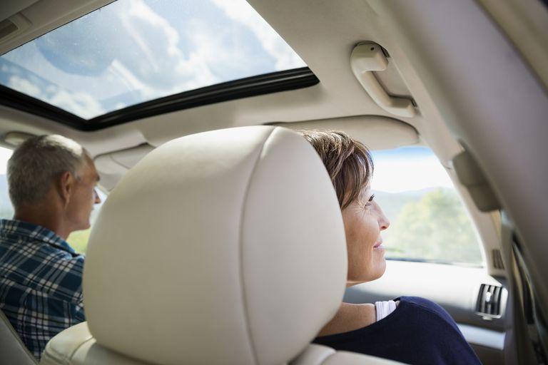 mature couple enjoy sunroof in car