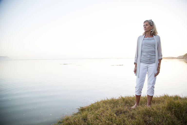 serious introspective looking woman standing at edge of lake