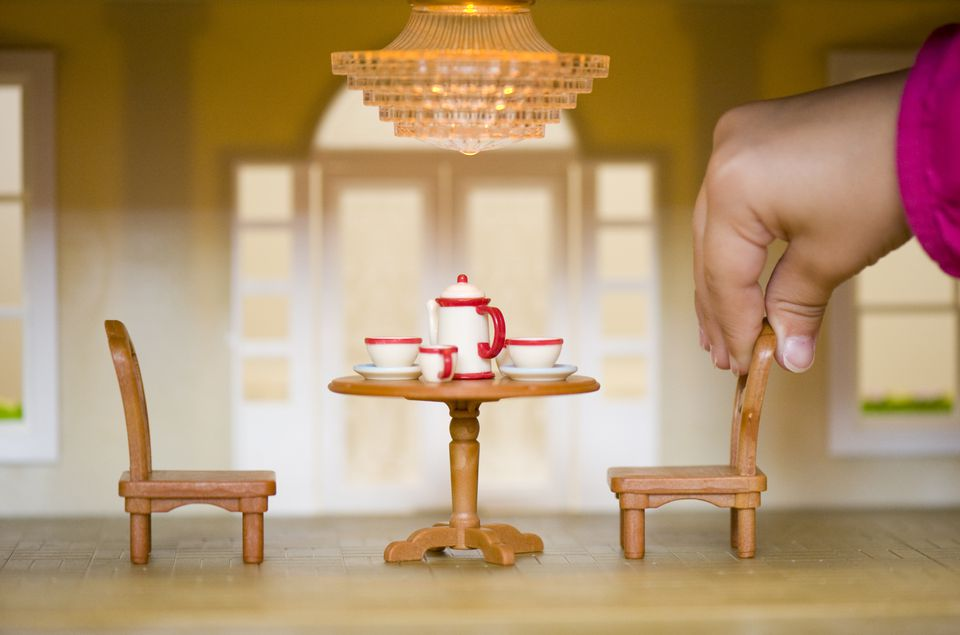Close up of child's hand in a dolls house