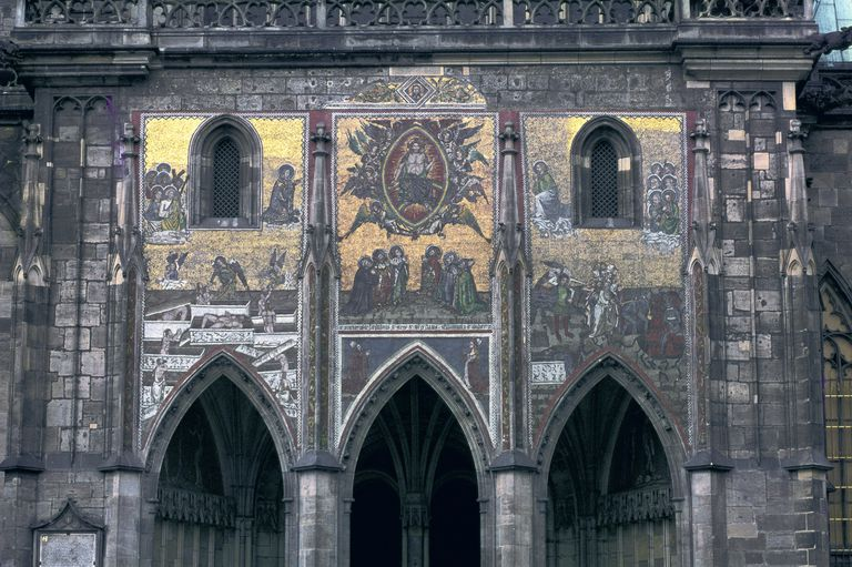 Close-up view of St. Vitus cathedral reveals two window eyes and a row of arched doorway teeth