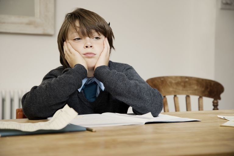 BOY SITTING AT TABLE WITH HOMEWORK LOKKING SAD