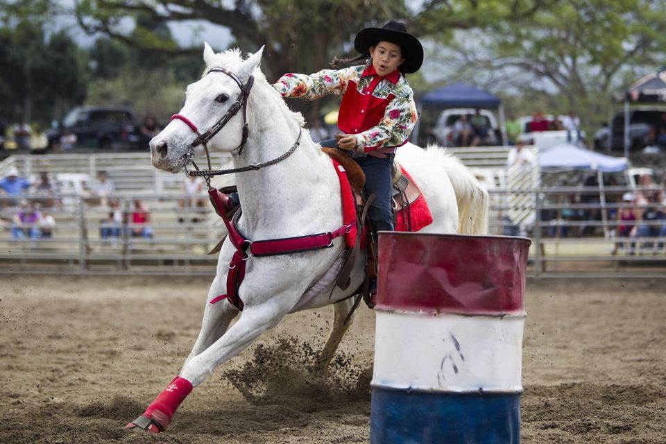 Young girl rider in rodeo barrel race