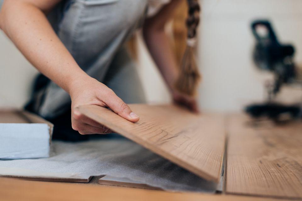 woman installing laminate wood floor
