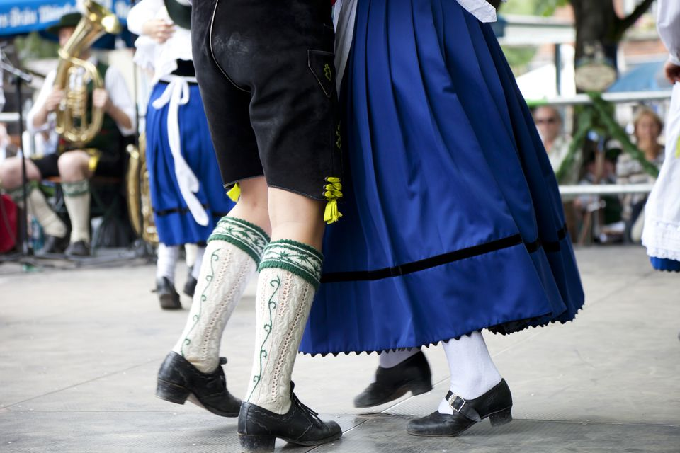 Bavarian couple in traditional outfits at Oktoberfest dance