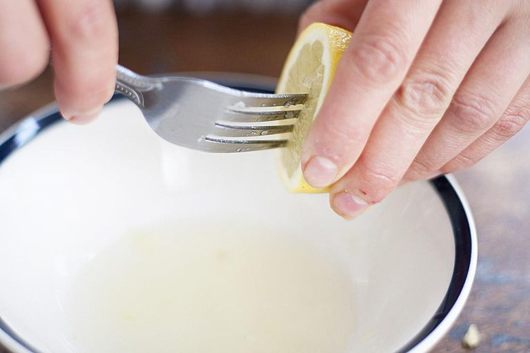 Squeezing juice from lemon with fork