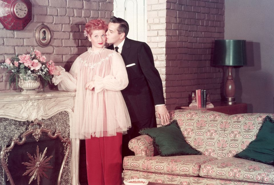 American actor and comedian Lucille Ball receives a kiss on the cheek from her husband, Cuban-born bandleader and musician Desi Arnaz, on the set of their television series, 'I Love Lucy'.