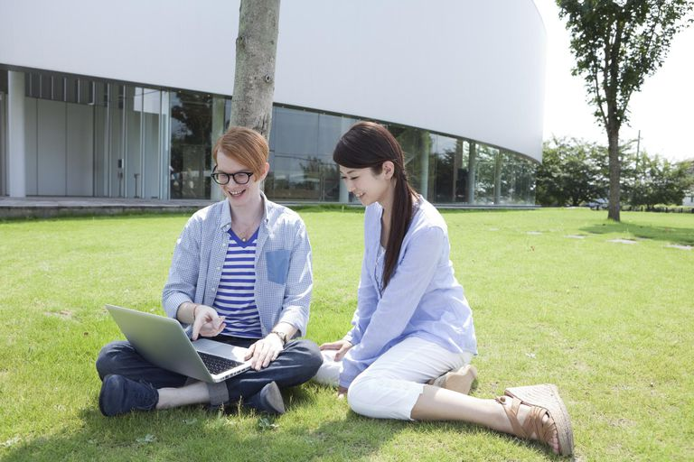 Young man and woman using laptop on lawn S...
