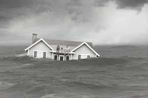 3 people sitting on top of ahouse that is half submerged in water