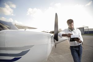Young pilot standing by his plane looking at paper