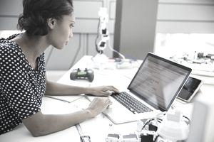 Engineer using laptop at desk with robotics