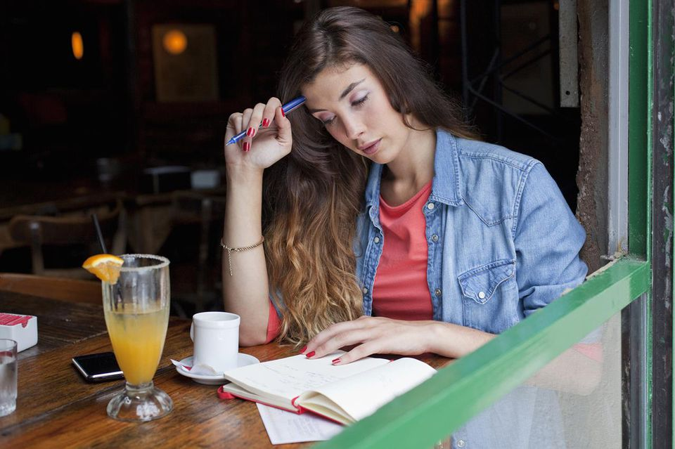 Young woman at a café table, writing in notebook