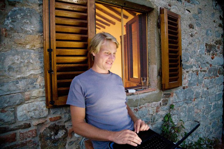 Man with laptop outside lighted window