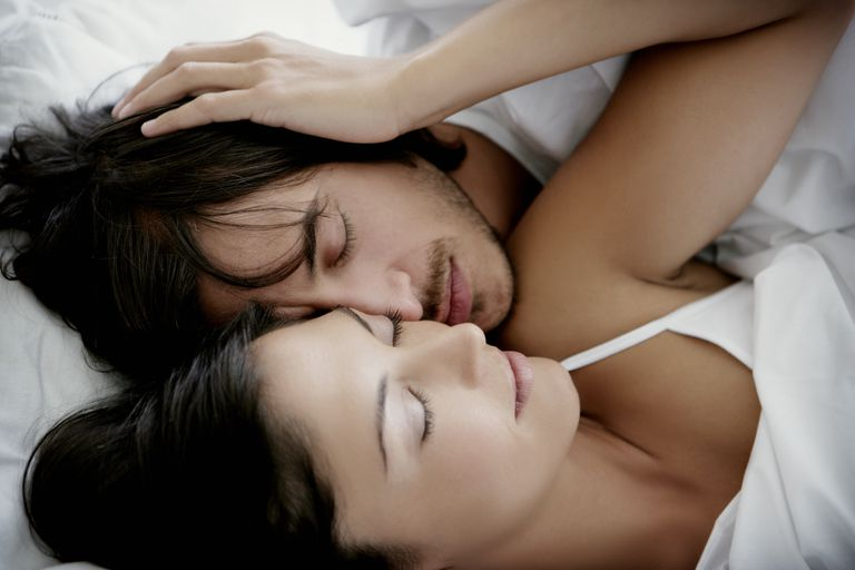 Couple cuddling in bed, intimacy to improve sex while trying to conceive