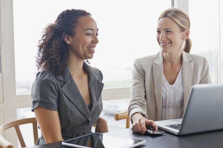 Two women talking at desk