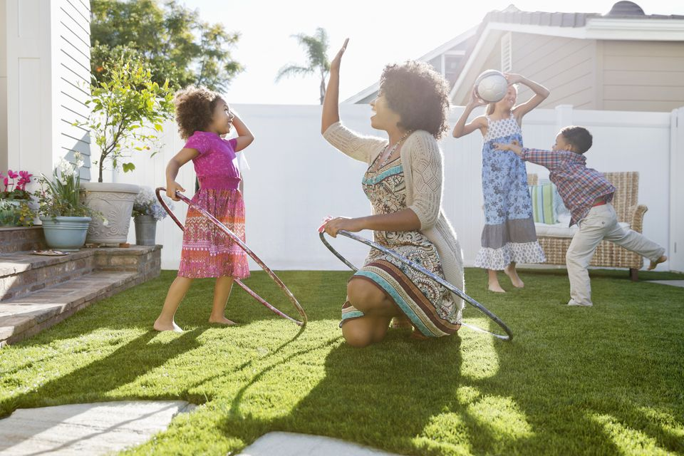 Cheerful mother and daughter with hula hoops giving high five on lawn