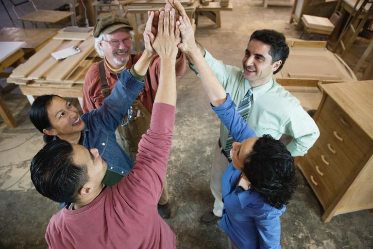 Businessman and colleagues giving each other high five in workshop, elevated view