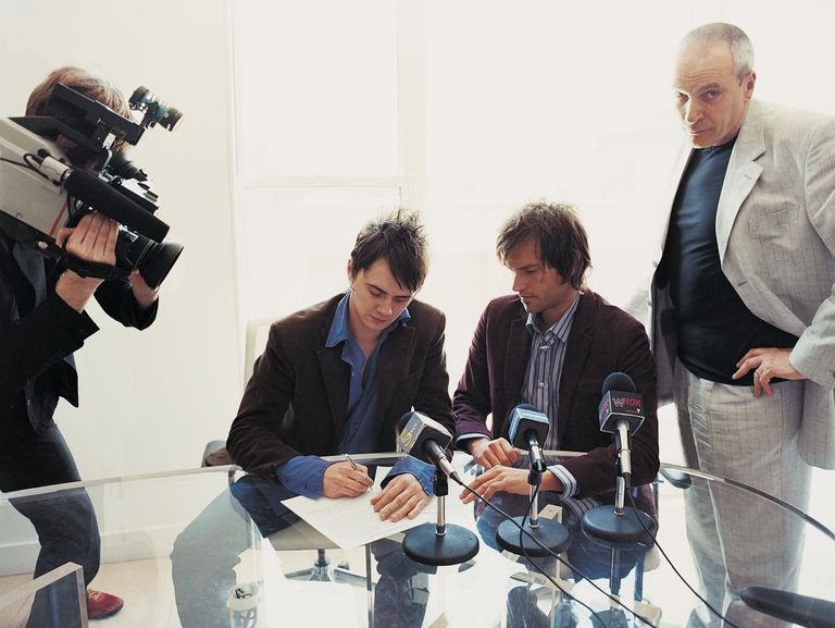 Pop Musicians Signing a Contract in a Conference Room Attended by Their Manager and a TV
