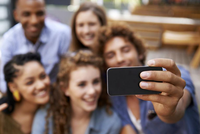 Group of friends taking a photo of themselves on a camera phone