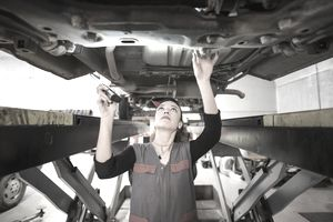 Mechanic inspecting for aftermarket or OEM parts on car