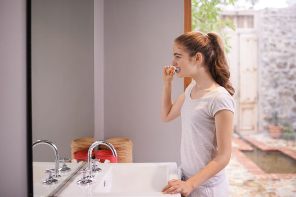 teen girl brushing teeth