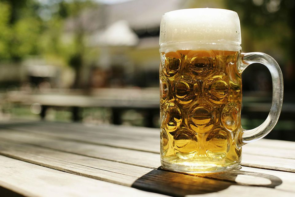 Stein of beer on a wooden table, close-up, selective focus