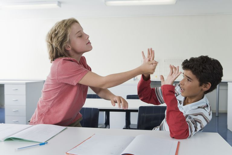 School boys (10-13) in classroom fighting, one boy hitting the other, bullying