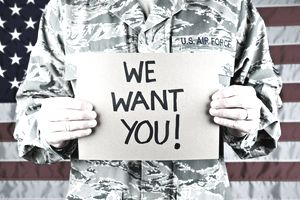 "man in Air Force uniform holding ""we want you!"" sign"