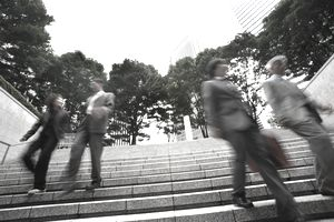Four executives walking down stairway, low angle view (blurred motion)