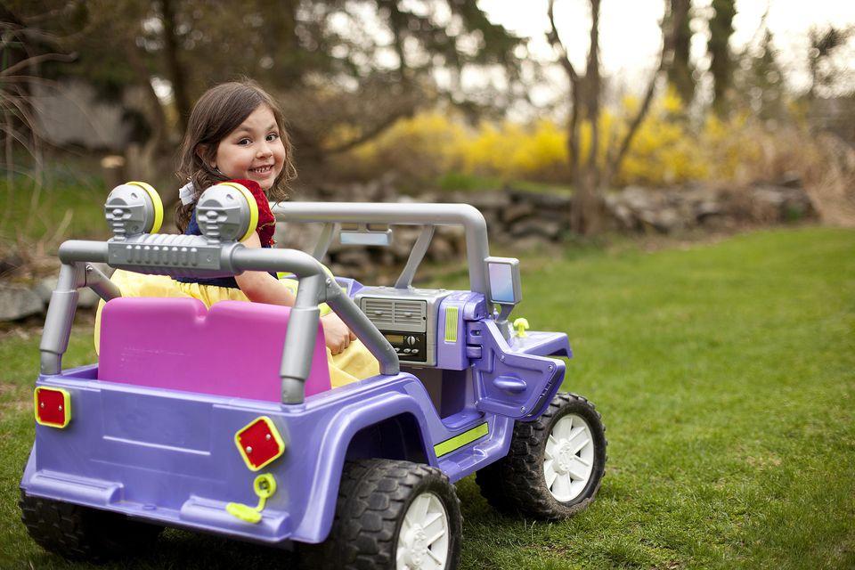 Little girl wearing costume in power wheels car