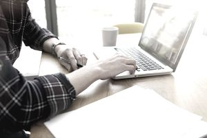 man working on cover letter on laptop