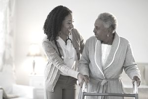 Nurse aiding woman with walker
