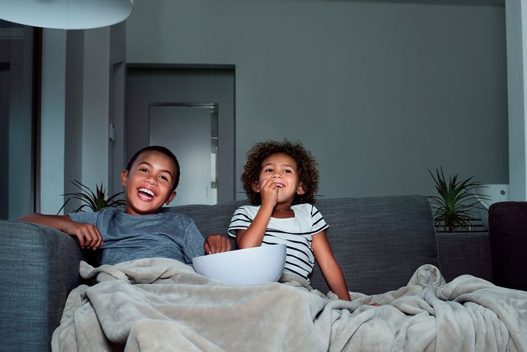 Happy siblings having popcorn while watching TV in living room at home.