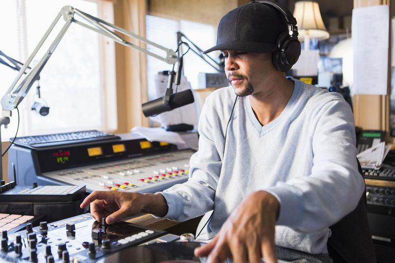 Mixed race disc jockey using turntable in studio