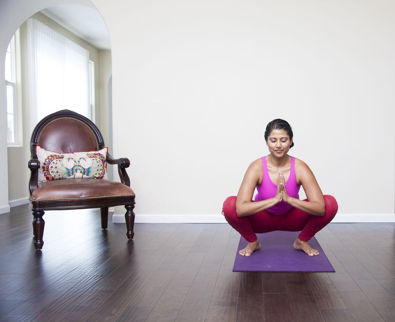 Asian woman practicing yoga in living room