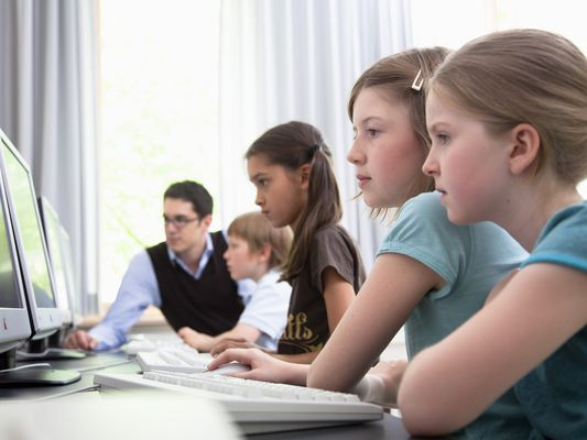 Male teacher helping pupils in computer room