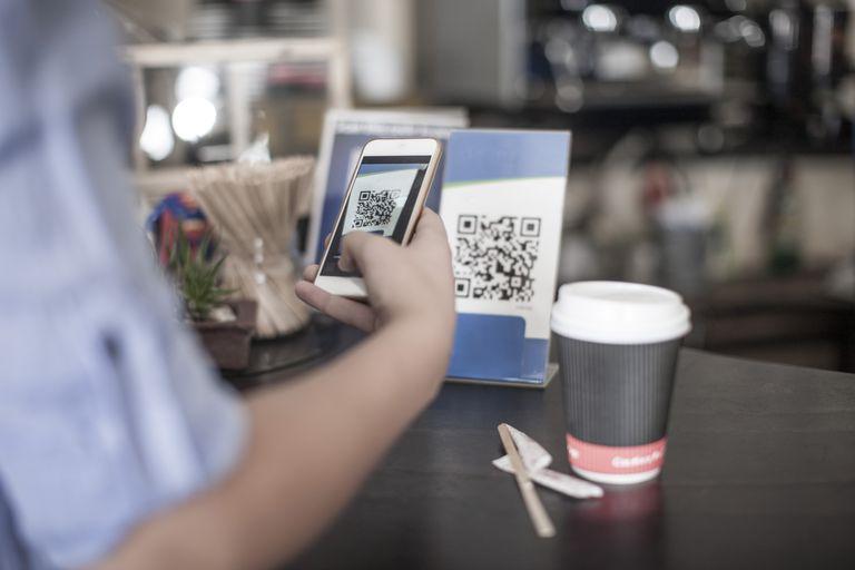 Hand holding smart phone, scanning QR code