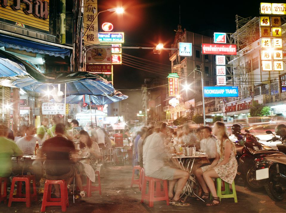 People dining at street food stalls in Bangkok.