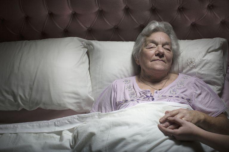 Young woman holding sleeping senior woman's hand