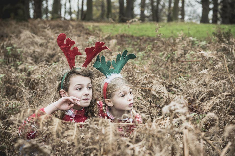 Two girls hiding in bracken wearing reindeer antlers