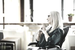 Mature businesswoman listening and thinking at her desk