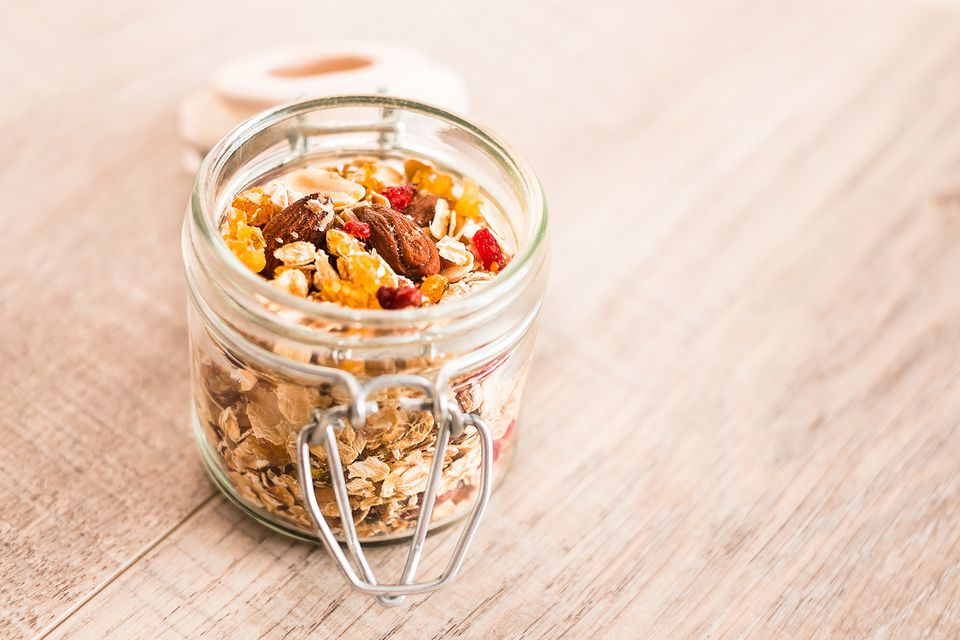 Homemade muesli with oat flakes, dried fruits and nuts in a jar, selective focus.