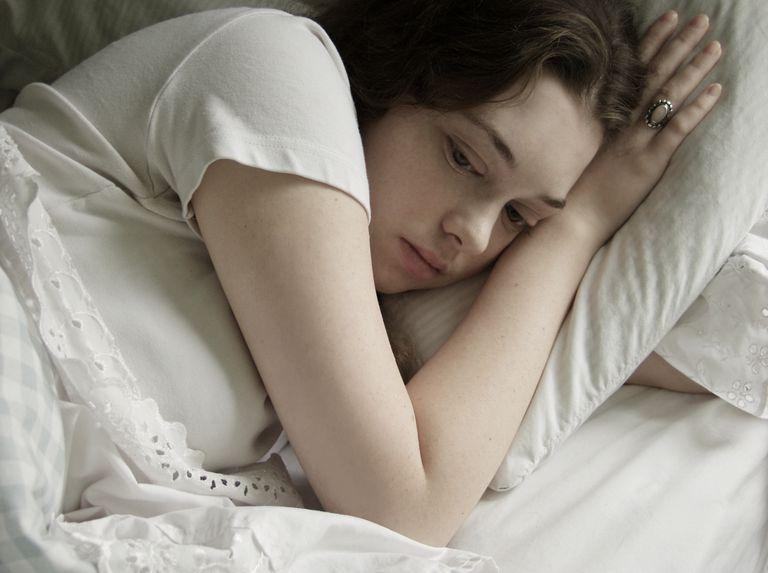 Sad woman awake in bed