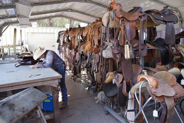 Saddler working in his saddle shop