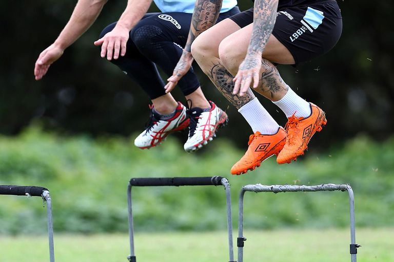 John Morris and Todd Carney jump hurdles during a Cronulla Sharks NRL training session at Sharks Stadium on April 8, 2014 in Sydney, Australia.