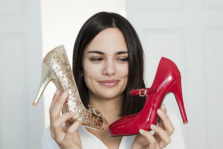 Young woman choosing between shoes
